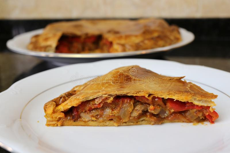 Meat pie traditional home cooking. The meat empanada is a traditional Andalusian and Spanish home cooking meal. The pie is on a white plate on a dark background stock photo