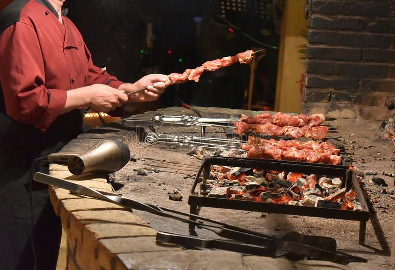 Meat in hand pierced with skewers at the stake royalty free stock image