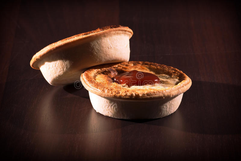 Meat Pies with sauce and high contrast lighting. Freshly baked meat pies with sauce and high contrast lighting royalty free stock image