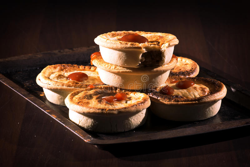 Meat Pies with sauce and high contrast lighting. Freshly baked meat pies with sauce and high contrast lighting stock image