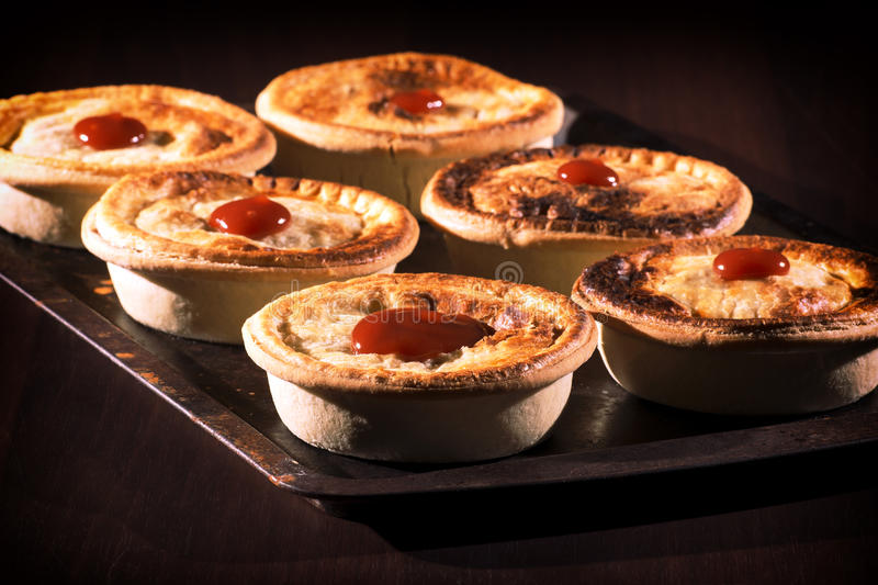 Meat Pies with sauce and high contrast lighting. Freshly baked meat pies with sauce and high contrast lighting stock photo