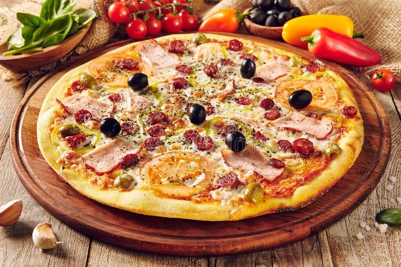 Meat pizza on wooden table close up stock photo