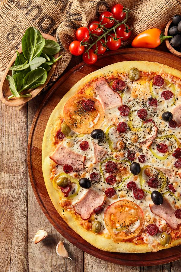 Meat pizza on wooden table stock image