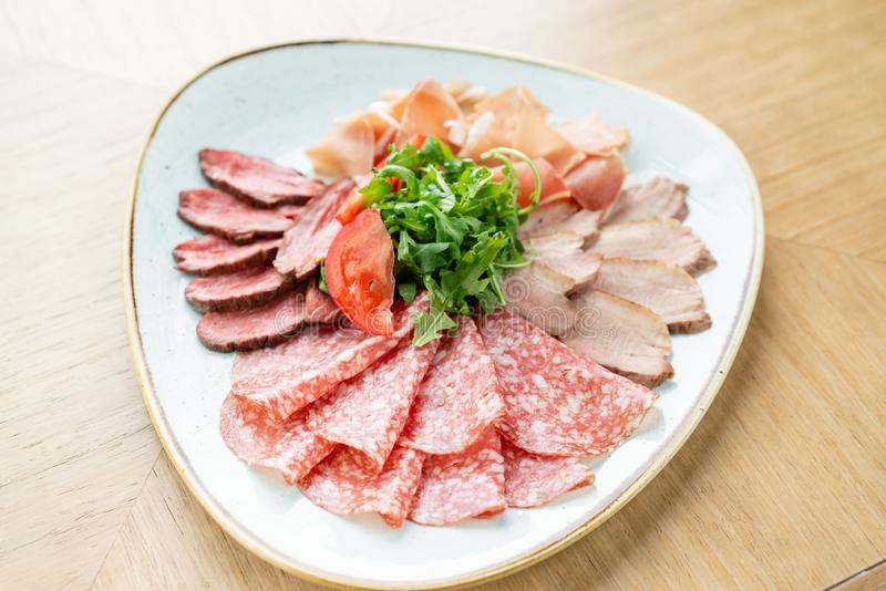 Meat plate, delicacy and Anantipasto. Salami, roast beef, Parma ham, smoked duck breast. Restaurant menu. royalty free stock images