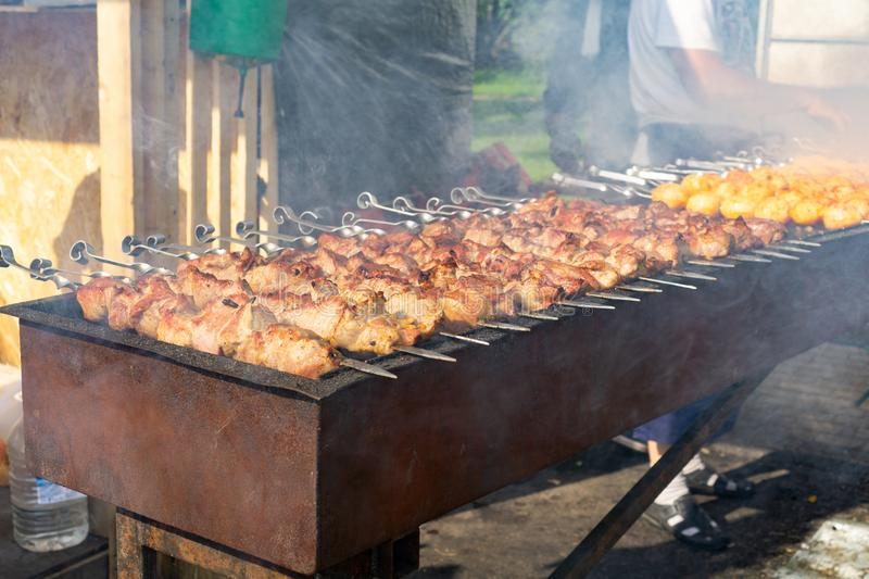 Meat and potato on skewers preparing on open grill by chef during bbq festival. Selective focus. Russia, Moscow, 26-28th July 2019. BBQ festival in Moscow stock photo