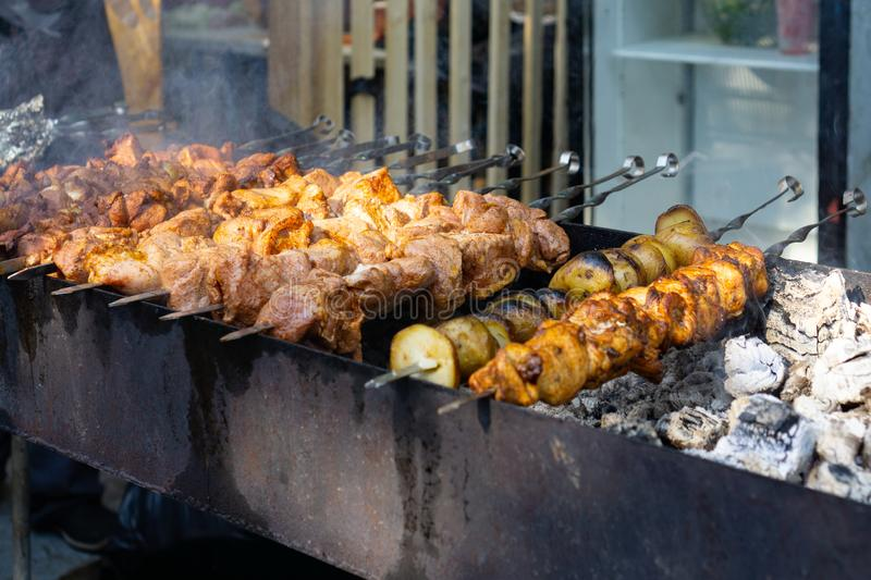 Meat and potato on skewers preparing on open grill by chef during bbq festival. Selective focus. Russia, Moscow, 26-28th July 2019. BBQ festival in Moscow royalty free stock photography