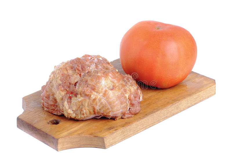Meat product.and tomato on a cutting board royalty free stock photo
