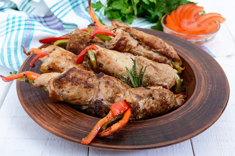 Meat rolls stuffed with sweet pepper, carrots in a clay bowl on a white wooden background royalty free stock photo