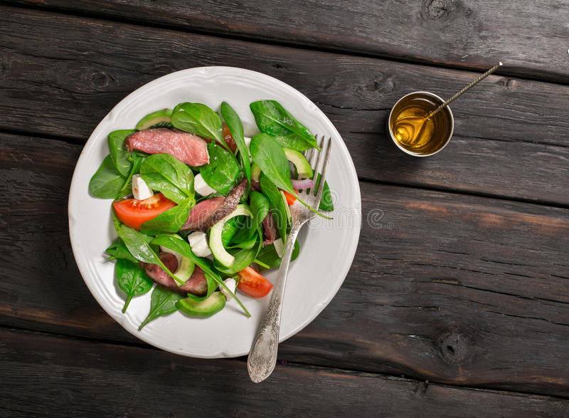 Meat salad and dressing near on the dark wooden table stock images