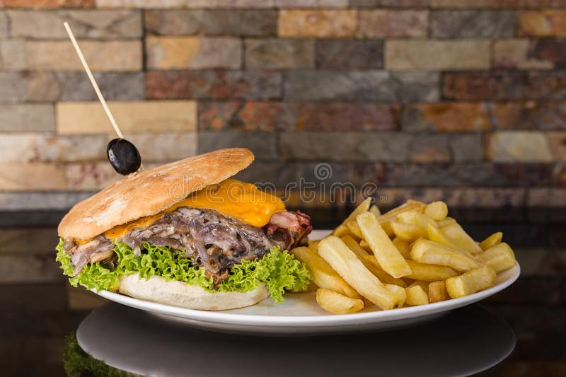 Meat sandwich with cheddar cheese, mushrooms, onion, lettuce, tomato, bacon and french fries. Food breakfast bread grilled refreshment nobody launch hamburger stock photography