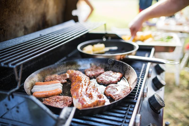 Meat and sausages on the grill. Garden party outside in the backyard. stock photos