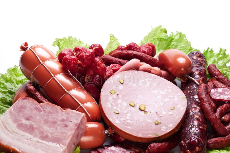 Meat and sausages on lettuce leaves. stock images