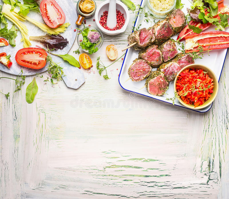Meat skewers with fresh herbs, spices and vegetables ingredients for grill or cooking. Preparation on light wooden background, top. View, border stock photos