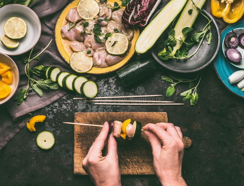 Meat skewers making. Female hands put meat on a skewer on wooden kitchen table background with chicken pieces and vegetables stock image
