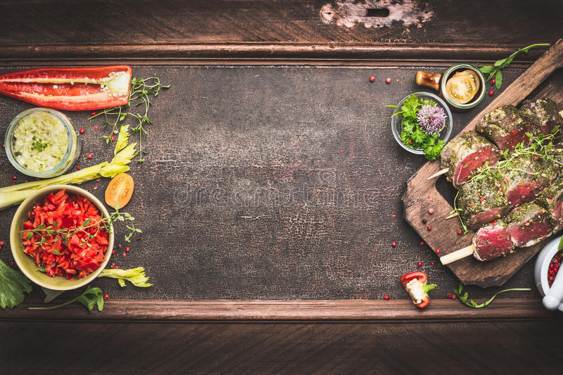 Meat skewers with vegetables and fresh flavoring, preparation for grill or BBQ on dark vintage background, top view. Banner stock images