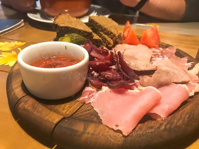 Meat snack with alcohol from meat, ham, basturma with sauce on wooden stands on the table in a cafe, bar, restaurant royalty free stock photos