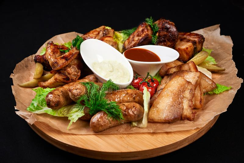 Meat and snack set. pub, restaurant, bar food concept. meat appetizers set with grill chicken, sausages, tomatoes cherry, souses royalty free stock photo