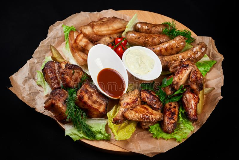 Meat and snack set. pub, restaurant, bar food concept. meat appetizers set with grill chicken, sausages, tomatoes cherry, souses. And fresh greens stock photo