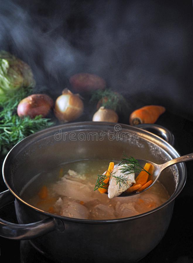 Meat soup with fresh vegetables cooked on the stove. Hot soup in meat broth in a saucepan with handles. Steam over a pot of soup. Raw vegetables are on the stock photos