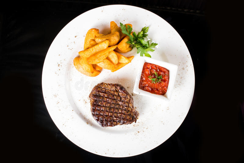 Meat steak with potatoes. Juicy meat steak with potatoes and sauce closeup royalty free stock images