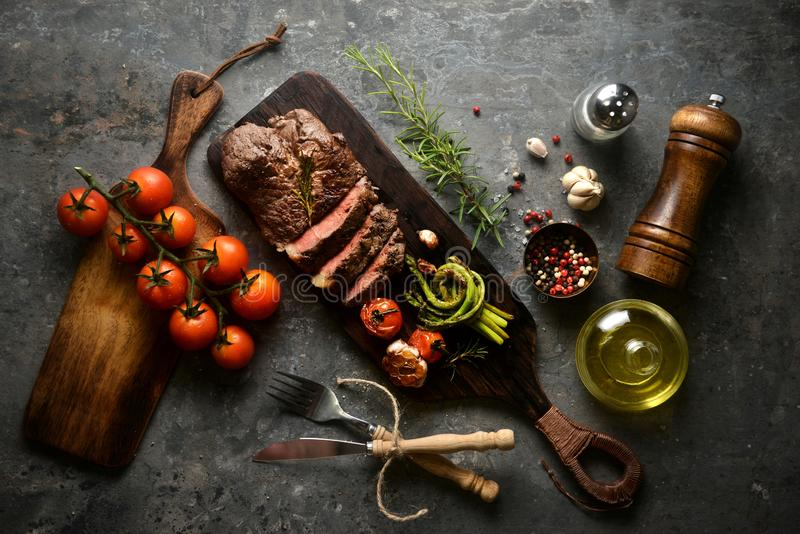 Meat steak serving on wooden butcher board with various ingredients surrounding,with fork and knife.top view, horizontal image. Asparagus, background, bbq stock photo