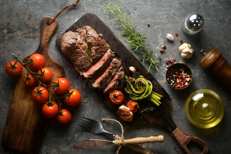 Meat steak serving on wooden butcher board with various ingredients surrounding,with fork and knife.top view, horizontal image. Asparagus, background, bbq royalty free stock image