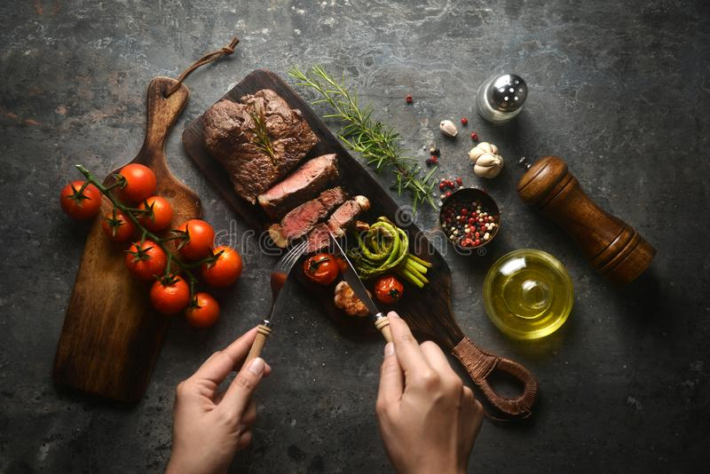 Meat steak serving on wooden butcher board with various ingredients surrounding, and hands holding fork and knife to cut a pieces. Of meat grilled. top view stock images
