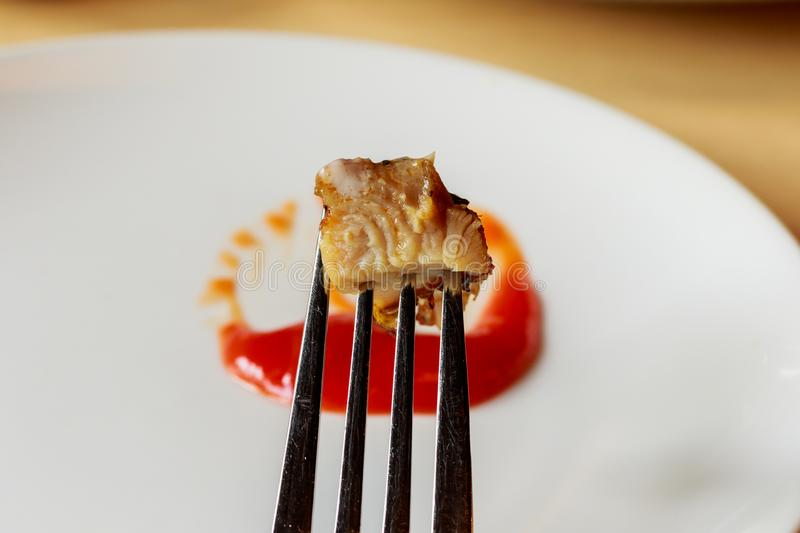 Meat steak stab in fork dipping spicy sauce.  stock photography
