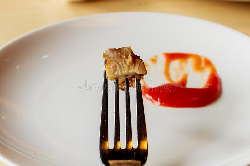 Meat steak stab in fork dipping spicy sauce.  stock image