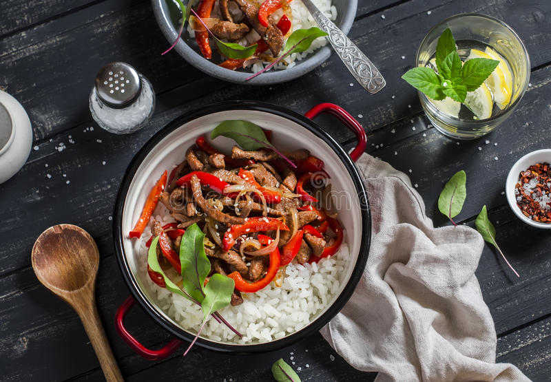 Meat stir fry with red peppers and rice in a pot, homemade lemonade with lemon on a dark wooden background. Delicious healthy. Lunch. Top view royalty free stock photos