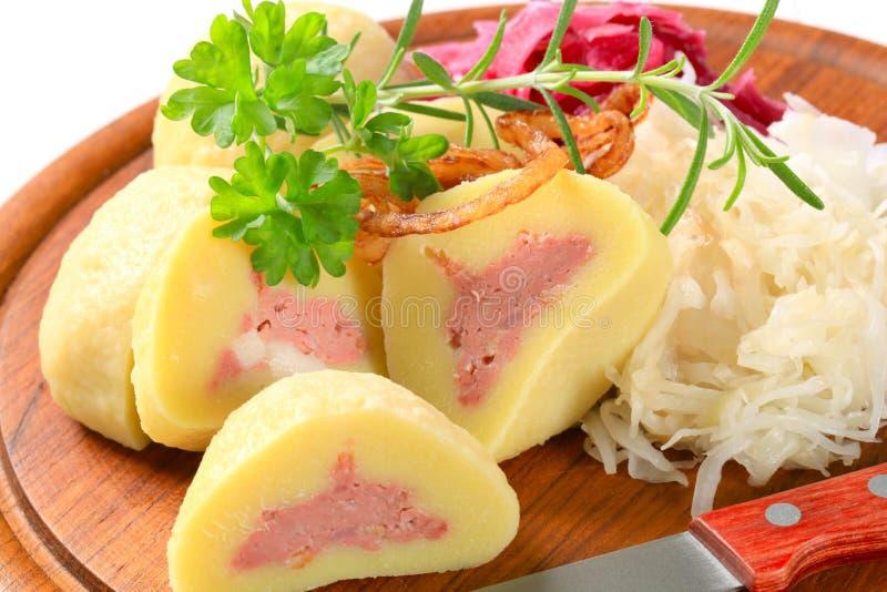 Meat stuffed potato dumplings with shredded cabbage stock image