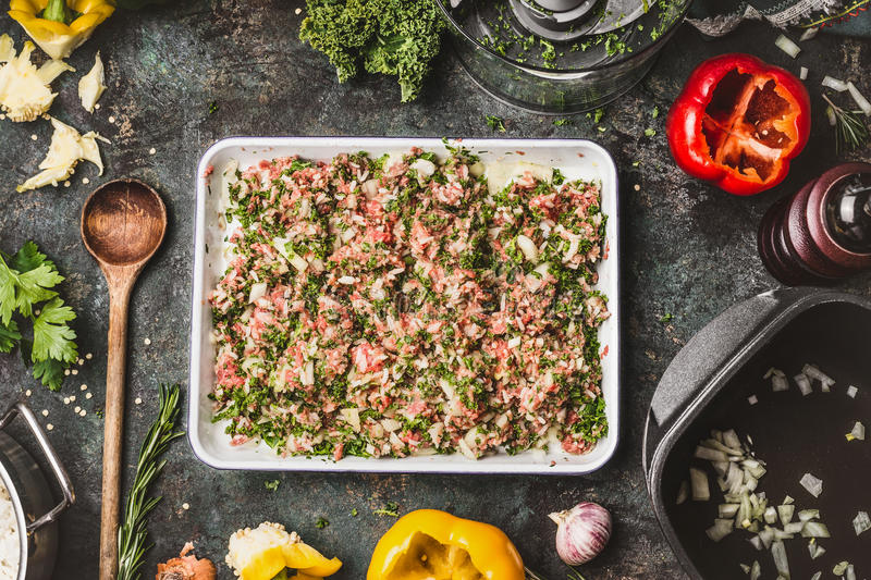 Meat stuffing with ground meat, rice and chopped kale for paprika filling on rustic kitchen table background with wooden cooking stock photography