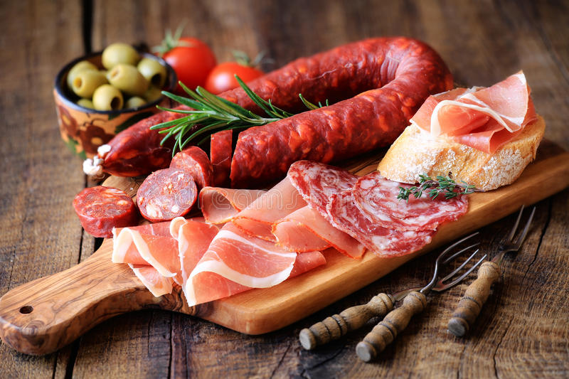 Meat tapas. Cured meat platter of traditional Spanish tapas - chorizo, salsichon, jamon serrano, lomo - erved on wooden board with olives and bread royalty free stock image