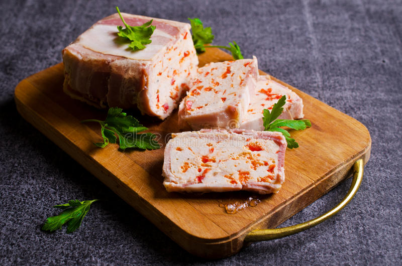 Meat terrine with bacon. And paprika on a dark background. Selective focus royalty free stock image