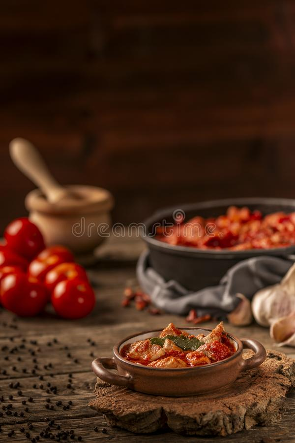 Meat and tomato meal with fresh vegetables and ingredients on dark background stock photography
