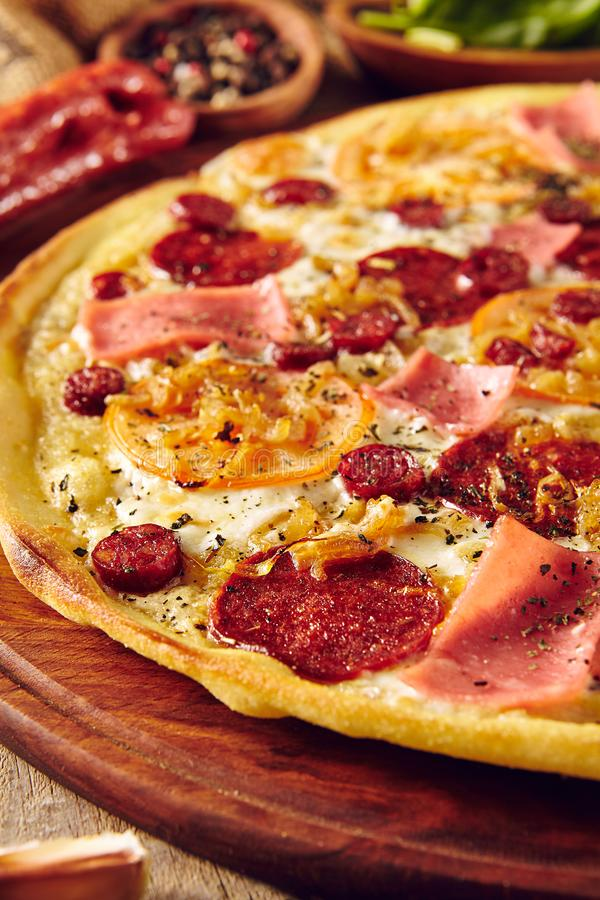Meat and tomato pizza on wooden table close up stock images