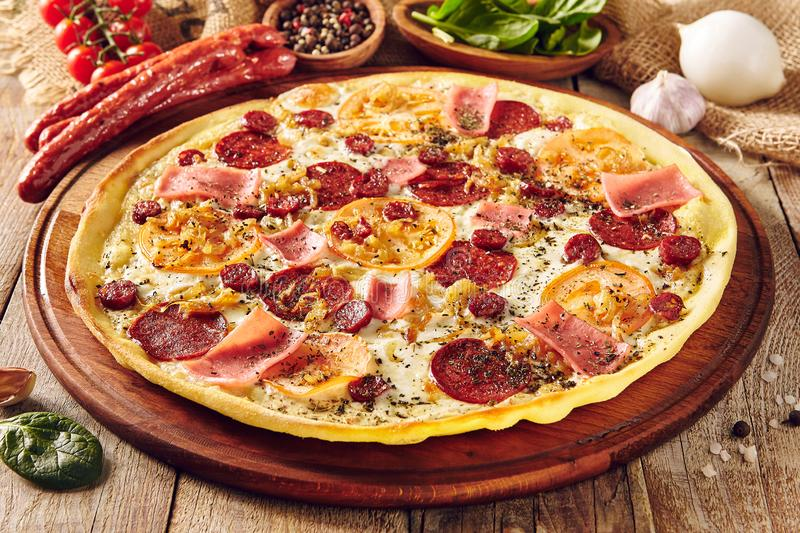 Meat and tomato pizza on wooden table close up royalty free stock image