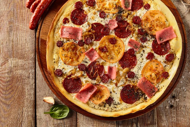 Meat and tomato pizza on wooden table stock photo