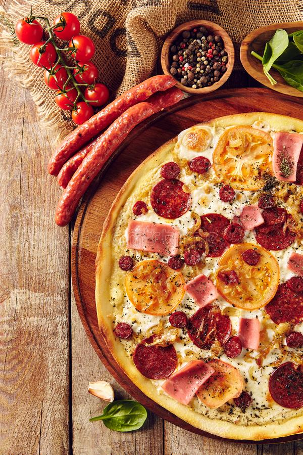 Meat and tomato pizza on wooden table top view royalty free stock images