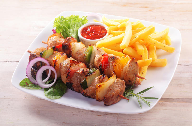 Meat and Vegetable Kebabs Served with French Fries royalty free stock photography