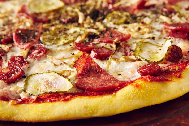 Meat and vegetable pizza on wooden table close up stock images