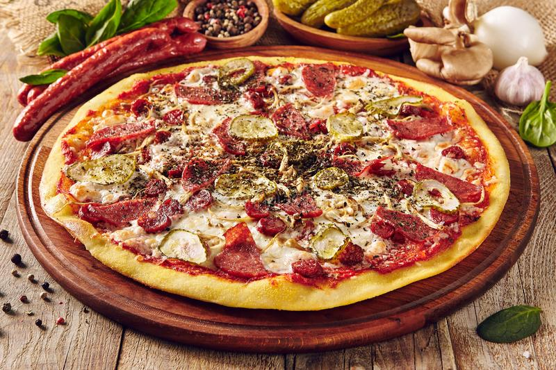 Meat and vegetable pizza on wooden table close up royalty free stock photography