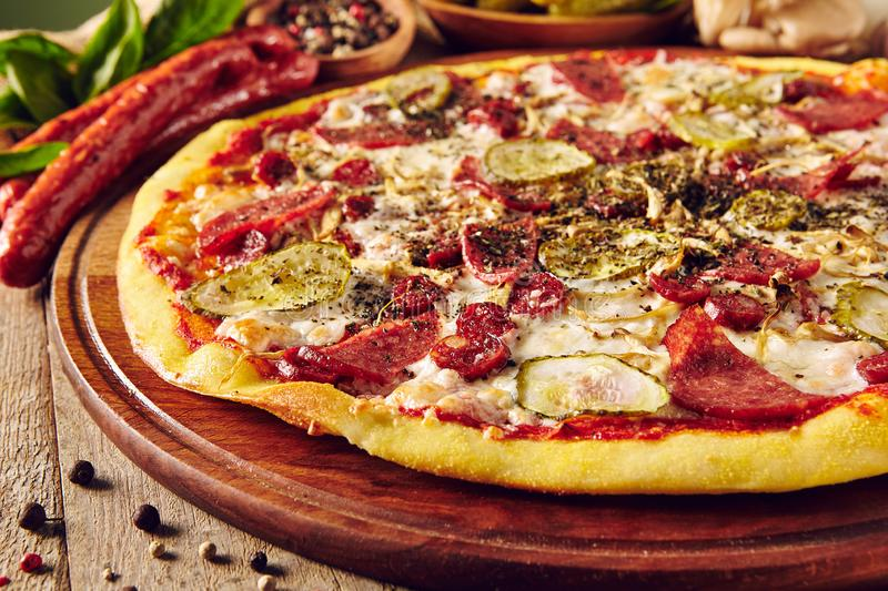 Meat and vegetable pizza on wooden table close up stock image