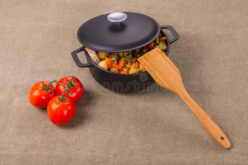 Meat and vegetables in the pan, and tomatoes next to the table. royalty free stock images