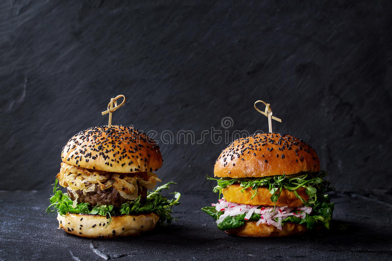 Meat and veggie burgers. Homemade traditional and veggie burgers with beef, fried onion, sweet potato, radish and pea sprouts, served over black textured stock photography