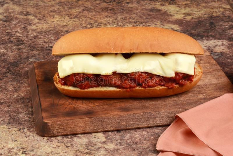 Meatball sub sandwich with mozzarella cheese. On a wood cutting board with napkin royalty free stock photo