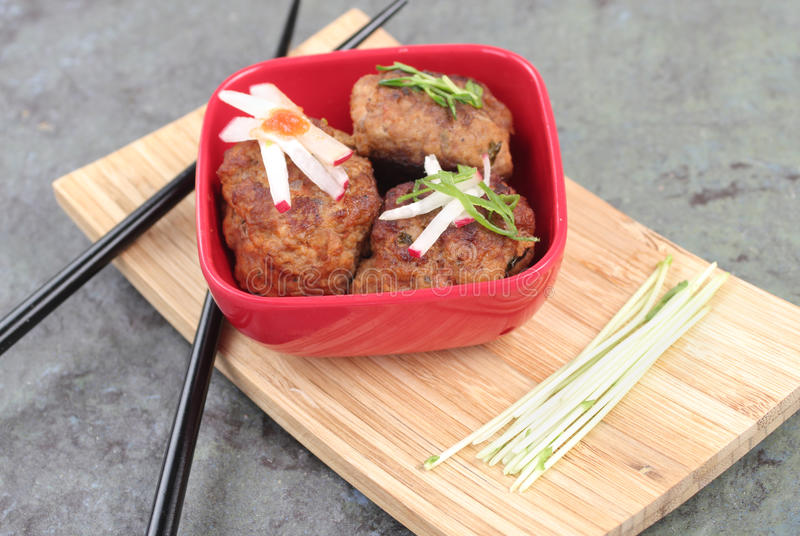 Meatballs Asian Style. Three meatballs with radish and parsley served in a red Asian bowl with chopsticks stock images