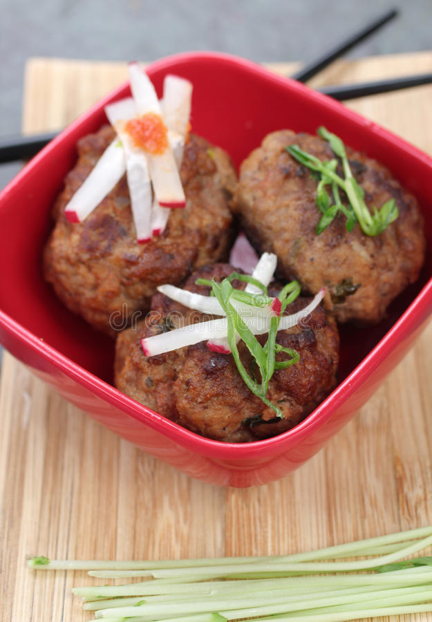 Meatballs Asian Style. Three Meatballs served Asian style with radish slices, in a red bowl with chopsticks stock images