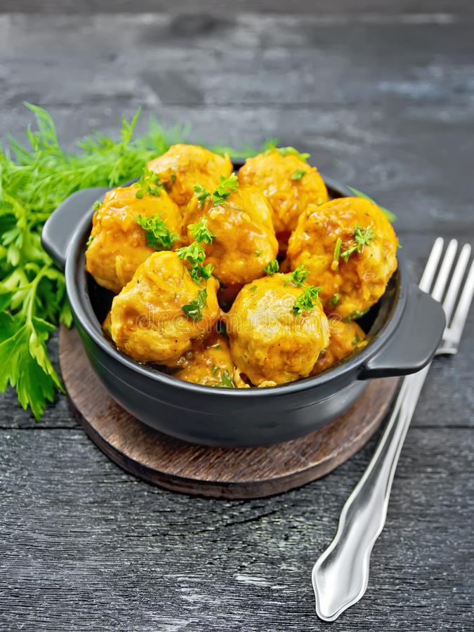 Meatballs in black brazier on board. Meatballs with tomato sauce in a brazier with parsley, dill, fork on a wooden plank background stock photos