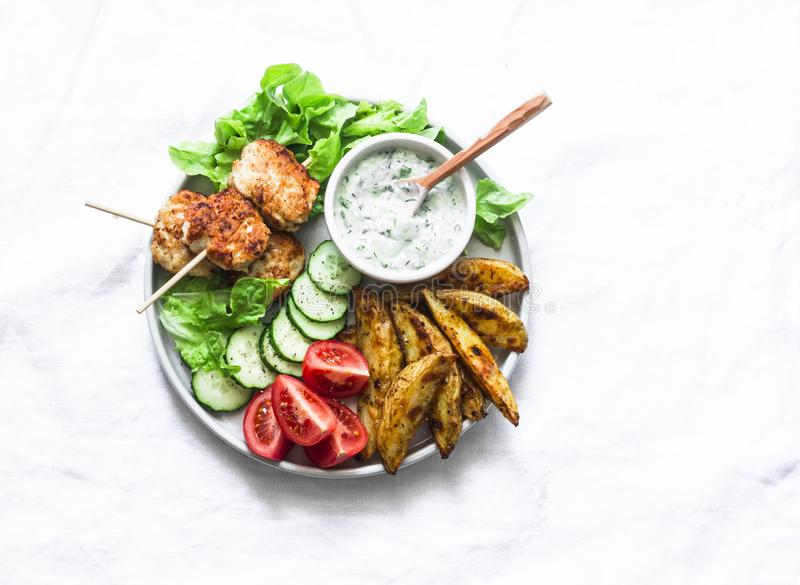Meatballs kebab, rustic baked potato, fresh vegetables and yogurt herb sauce on light background, top view. Summer picnic healthy stock photography